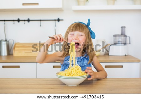 Portrait of a smiling little girl in a blue dress funny eats a spaghetti