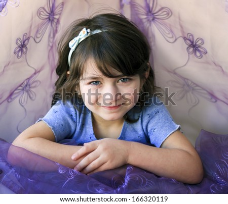 Portrait of a smiling little girl in blue and purple - stock photo