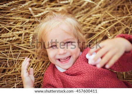 Portrait of a smiling little girl lies on a ears of wheat - stock photo