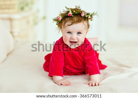 Portrait of a smiling little girl little girl in a red dress and a wreath of flowers, close-up - stock photo