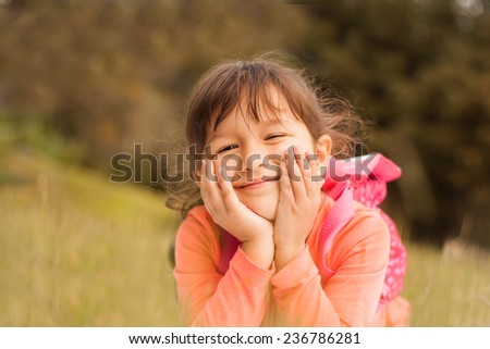 Portrait of a smiling little girl lying on green grass. - stock photo