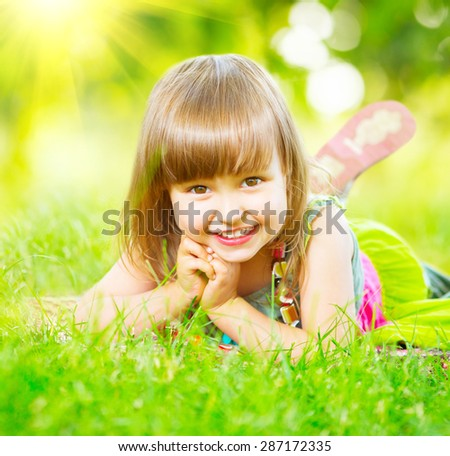 Portrait of a smiling little girl lying on green grass. Cute three years old child enjoying nature outdoors. Healthy carefree kid playing outside in summer park - stock photo