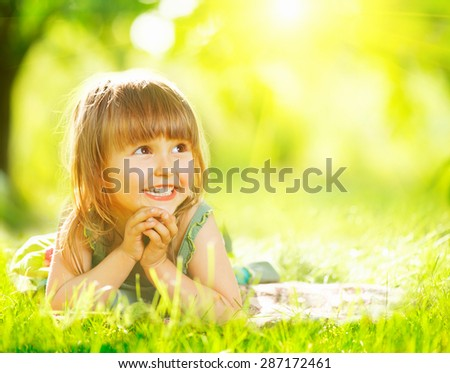 Portrait of a smiling little girl lying on green grass. Cute three years old child enjoying nature outdoors. Healthy carefree kid playing outside in summer park. Copy space for your text - stock photo