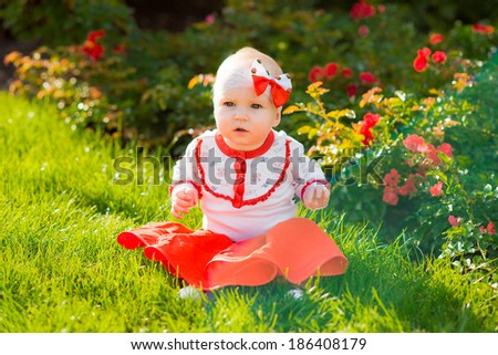 Portrait of a smiling little girl, lying on green grass in red skirt among roses