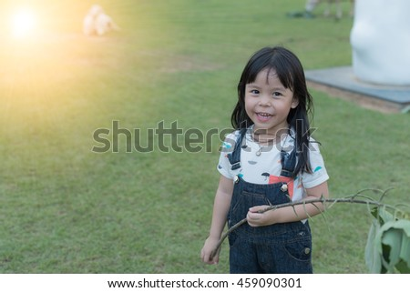 Portrait of a smiling little girl, on green grass (intentional sun glare)