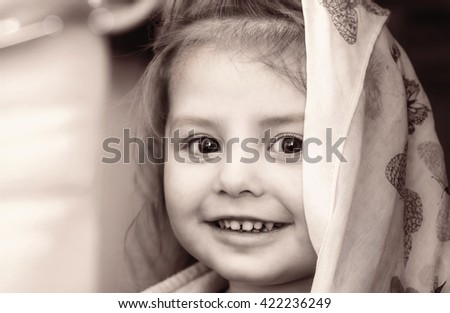 Portrait of a smiling little girl with headscarf in black white tones - stock photo