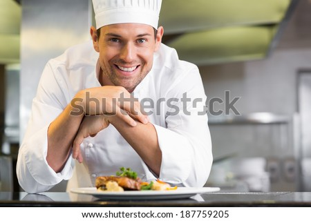 Portrait of a smiling male chef with cooked food standing in the kitchen - stock photo
