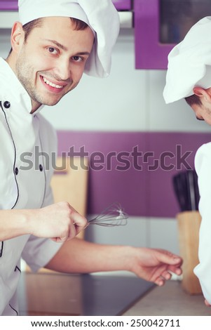 Portrait of a smiling male chef with his coworker cooking food and standing in the modern kitchen of restaurant. Indoor shot - stock photo