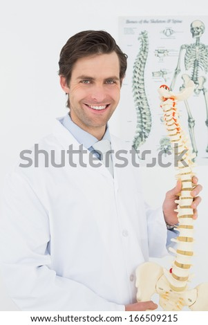 Portrait of a smiling male doctor holding skeleton model in his office - stock photo