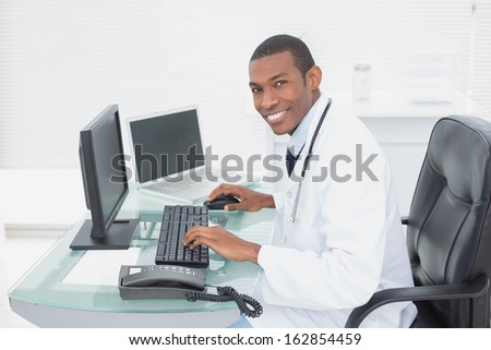 Portrait of a smiling male doctor using computer at medical office
