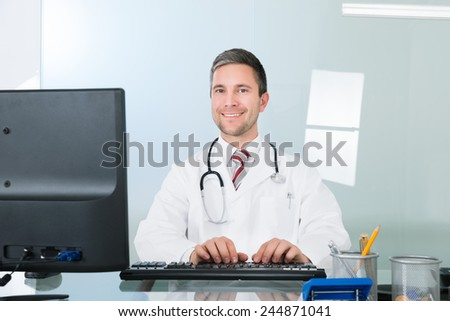 Portrait Of A Smiling Male Doctor Using Computer In Clinic - stock photo
