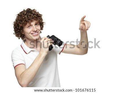 Portrait of a smiling male holding binoculars and pointing at blank copy space, over white background - stock photo