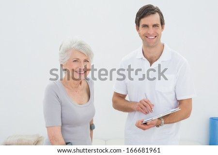 Portrait of a smiling male therapist and disabled senior patient in the gym at hospital - stock photo
