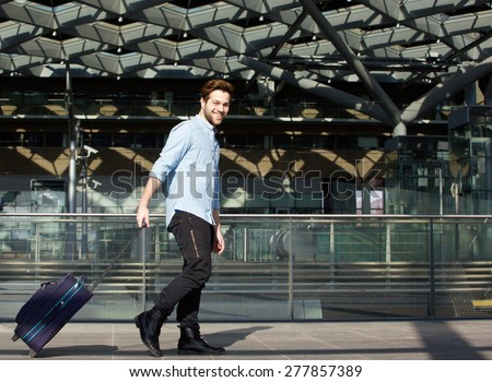 Portrait of a smiling male traveler walking with suitcase - stock photo