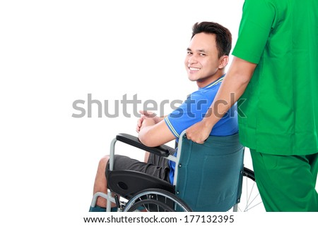 portrait of a smiling male with broken arm and foot using wheel chair. helped by the surgeon - stock photo