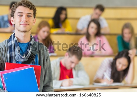 Portrait of a smiling male with students sitting at the college lecture hall