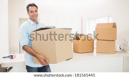 Portrait of a smiling man carrying boxes in a new house - stock photo