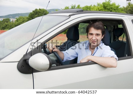 portrait of a smiling man driving his car - stock photo