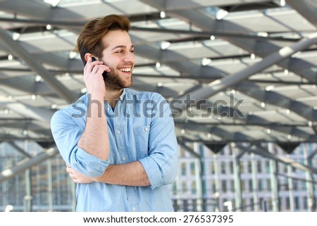 Portrait of a smiling man enjoying conversation on cell phone - stock photo