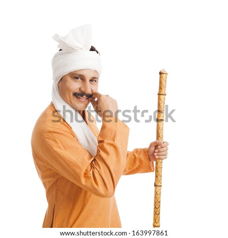 Portrait of a smiling man holing a staff and adjusting his mustache - stock photo