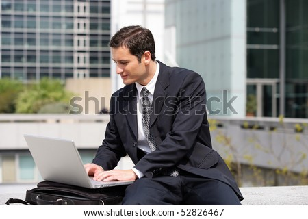 Portrait of a smiling man in front of a laptop computer - stock photo