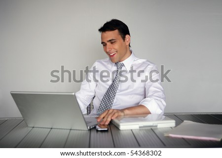 Portrait of a smiling man in suit in front of a laptop computer
