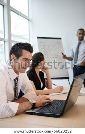 Portrait of a smiling man in the office to a laptop - stock photo