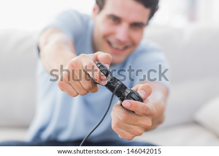 Portrait of a smiling man playing video games in his living room - stock photo