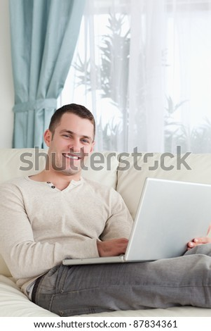 Portrait of a smiling man relaxing with a laptop in his living room