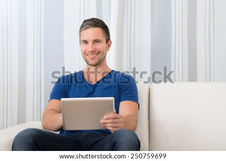 Portrait Of A Smiling Man Sitting On Couch Holding Digital Tablet - stock photo