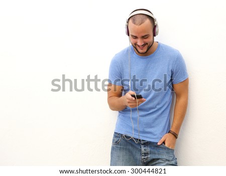 Portrait of a smiling man standing against a white wall with mobile phone and headphones - stock photo