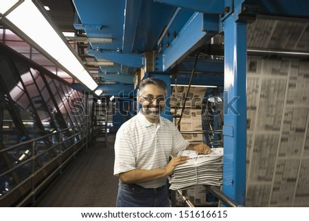 Portrait of a smiling man standing in factory with newspapers