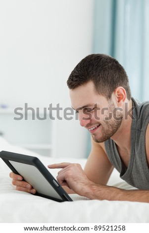 Portrait of a smiling man using a tablet computer while lying on his belly in his bedroom - stock photo