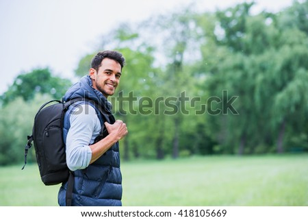 Portrait of a smiling man with a bag on green nature background. Travel