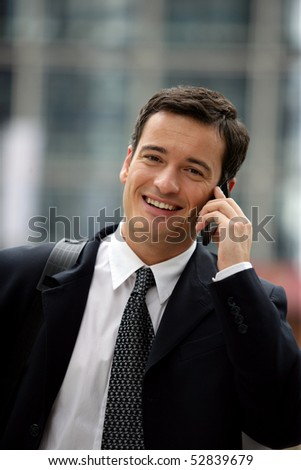 Portrait of a smiling man with a cell phone - stock photo