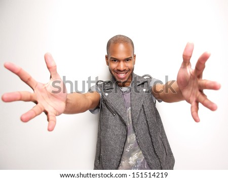 Portrait of a smiling man with arms outstretched and hands open - stock photo