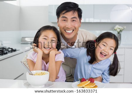 Portrait of a smiling man with happy two daughters having breakfast in the kitchen at home