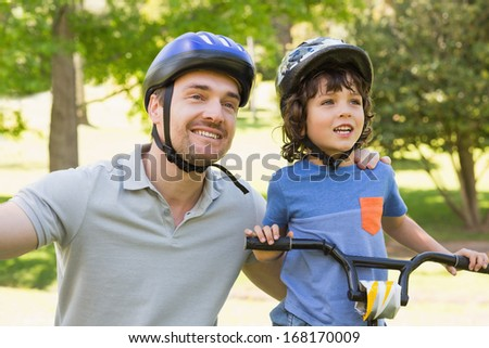 Portrait of a smiling man with his son riding bicycle - stock photo