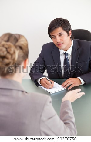 Portrait of a smiling manager interviewing a female applicant in an office - stock photo