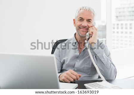 Portrait of a smiling mature businessman on call in front of laptop at desk in a bright office