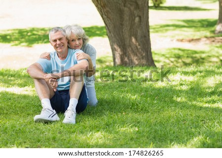 Portrait of a smiling mature couple sitting on grass at the park