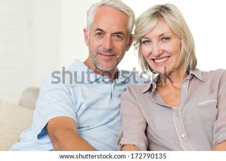 Portrait of a smiling mature couple sitting on sofa at home - stock photo
