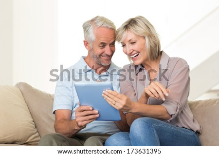 Portrait of a smiling mature couple using digital tablet on sofa at home - stock photo
