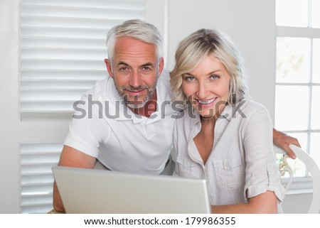 Portrait of a smiling mature couple using laptop at home