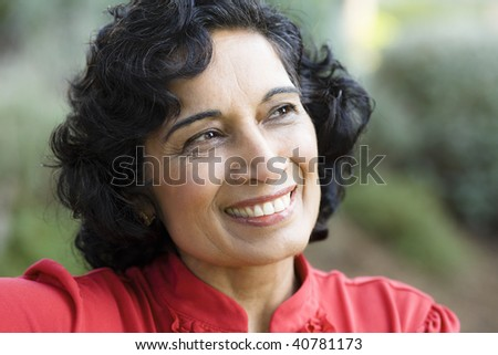 Portrait of a Smiling Mature Indian Woman Looking Away From Camera - stock photo