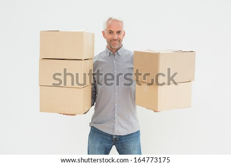 Portrait of a smiling mature man carrying boxes against white background