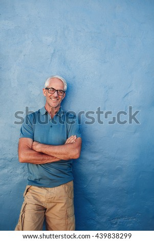 Portrait of a smiling mature man standing with his arms crossed. Caucasian middle aged man looking away at copy space and smiling. - stock photo