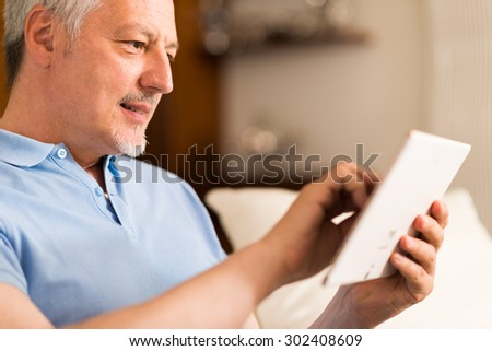 Portrait of a smiling mature man using a digital tablet in his living room - stock photo