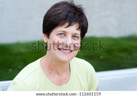 portrait of a smiling mature woman taken outside - stock photo