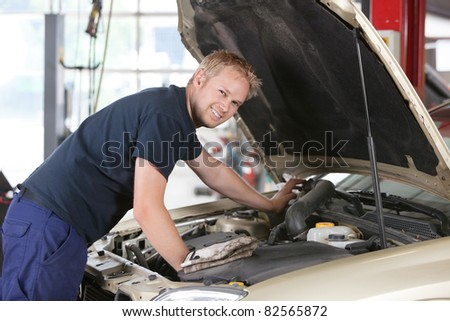 Portrait of a smiling mechanic working on a car in garage